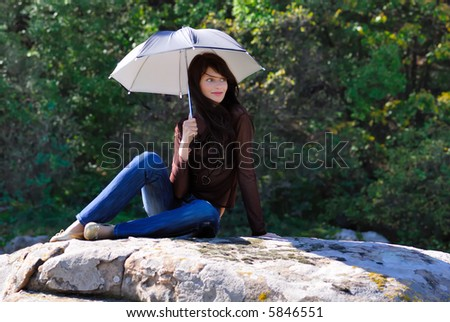 Smilling girl with umbrella on the stone - stock photo