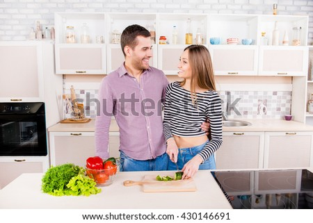 Smilling loving couple  cutting cuumbers for salad in the kitchen - stock photo