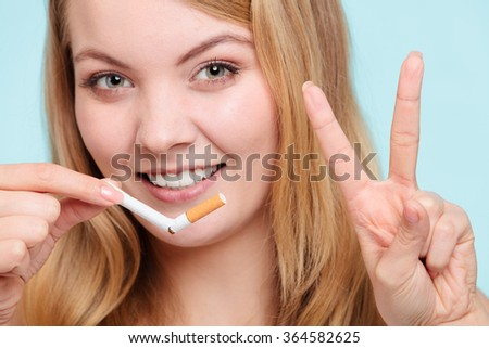 Smilling pretty girl breake down cigarette. Winning with addicted nicotine problems in young age giving victory gesture. Quitting from addiction concept. - stock photo