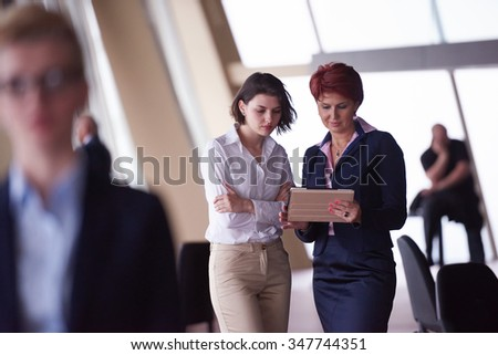 Smilling young business woman in front her team blured in background. Group of young business people. Modern bright  startup office interior.