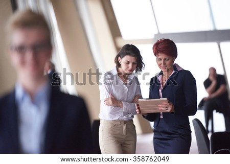 Smilling young business woman in front her team blured in background. Group of young business people. Modern bright  startup office interior. - stock photo