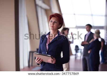 Smilling young business woman with tablet computer  in front her team blured in background. Group of young business people. Modern bright  startup office interior. - stock photo