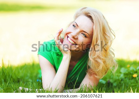 Smilng happy young woman lying on green grass meadow - stock photo