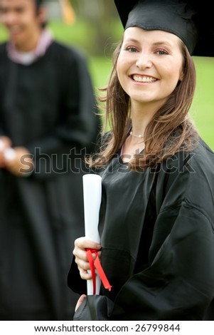 Smily female graduate standing outdoors with her diploma - stock photo
