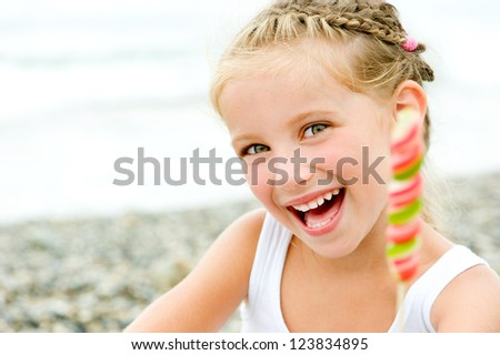 smily little girl with a candy on tropical beach vacation
