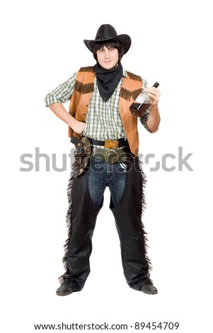 Smirking cowboy with a bottle of whiskey in hand - stock photo