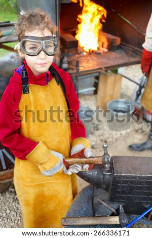smith girl in goggles and apron with hammer and anvil - stock photo