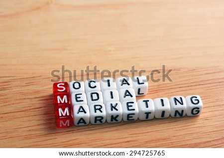 SMM Social Media Marketing written on dices on wooden background - stock photo