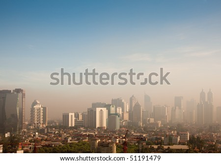 Smog dome and dust during sunrise in a very polluted city - in this case Jakarta, Indonesia - stock photo