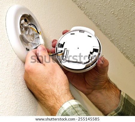 Smoke Alarm Being Repaired On Wall / Time To Check Your Smoke Alarms - stock photo