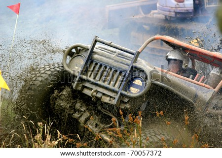 Smoke and mud spraying off an off road vehicle as it comes up the bank - stock photo