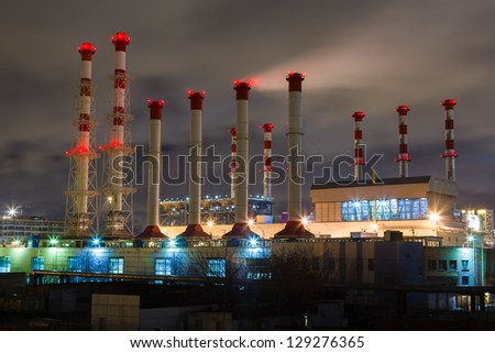 smoke and pipe plant with red lights in the night sky - stock photo