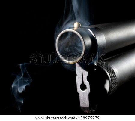 Smoke around and in the muzzle of a shotgun - stock photo