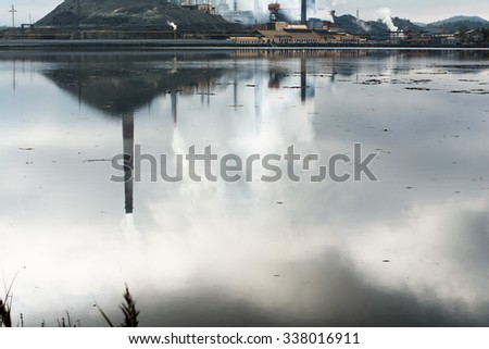 Smoke comes from one big chimney and a lot of small ones on grey sky background. Concept of air pollution - stock photo