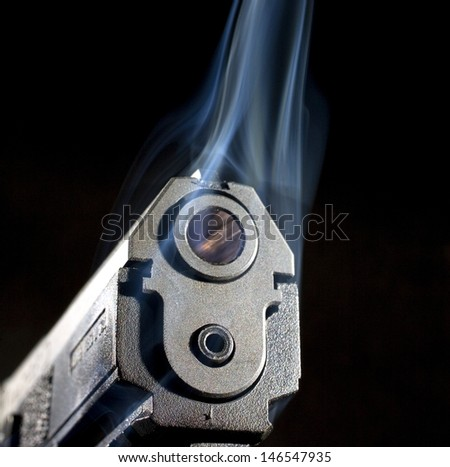 Smoke coming from around a handgun that has a polymer frame - stock photo