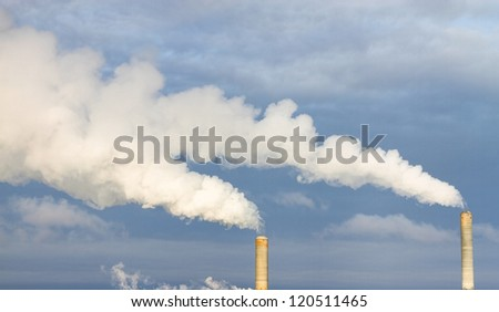 Smoke coming out of a stack at a powerplant - stock photo