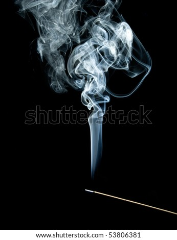 Smoke coming up from an incense stick over a black background - stock photo