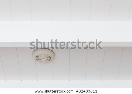 Smoke detector of fire alarm on white wooden ceiling. - stock photo