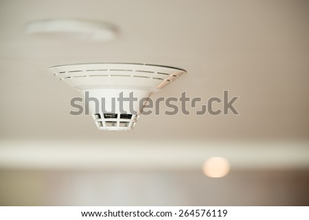 smoke detector on ceiling - stock photo