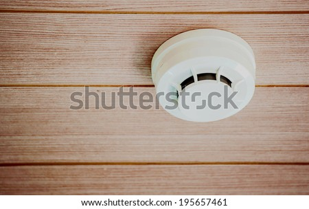 Smoke detector system on a vintage wooden ceiling - stock photo