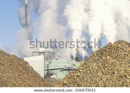 Smoke fills the air behind two large piles of logs lying in the yard of the Boise Cascade Paper Plant in Rumford, Maine - stock photo