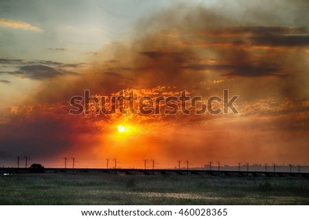 Smoke from a fire in a field at sunset - stock photo