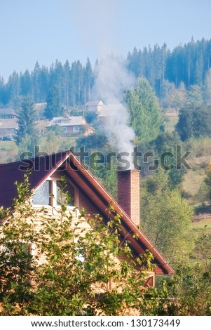 smoke from chimney of house in village - stock photo