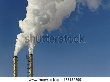 Smoke from chimneys on blue sky background. - stock photo