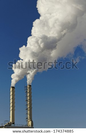 Smoke from chimneys on blue sky background.