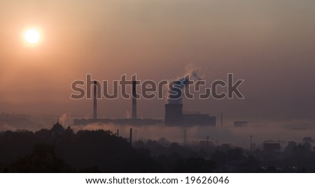 Smoke from factory over city in sunrise