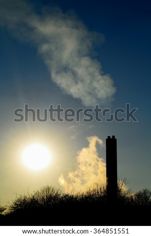 Smoke from factory with big chimney against blue sky