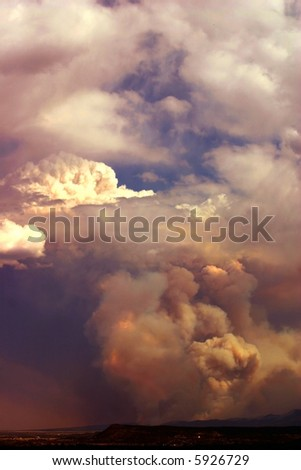 Smoke from forest fire billows up into the clouds. - stock photo