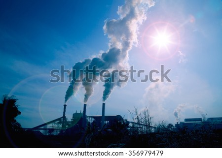 Smoke from silhouette industrial plant flow to sky with bright sun - stock photo