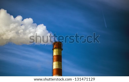 smoke from the chimney in the blue sky flying aircraft