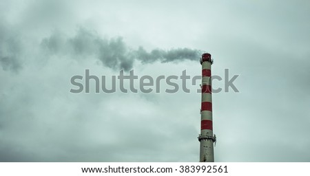 Smoke from the chimney of the plant against the dark sky - stock photo