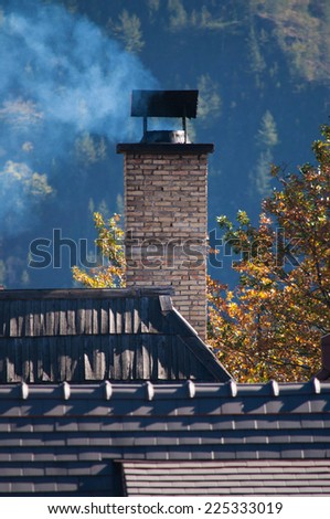 Smoke from the chimney on the house roof - stock photo