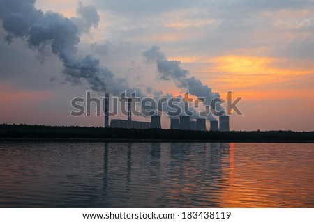 Smoke from the chimneys of a power plant at sunset