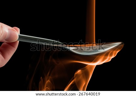 Smoke made to look like fire pouring on a spoon over a black background. - stock photo
