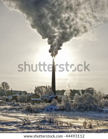 Smoke of thermal station. Frosty (cold) day. It is photographed against the sun. It is processed in graphic programs. - stock photo