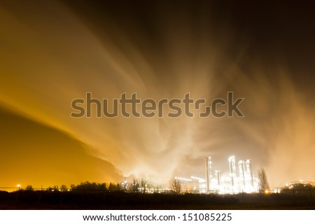 Smoke originating from a petrochemical plant at night - stock photo