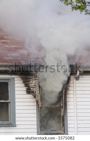Smoke pouring out of the second story window in a house that is on fire - stock photo