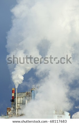 smoke produced by the smokestacks of a paper mill - stock photo