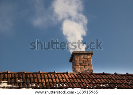 Smoke raising from a chimney in winter - stock photo