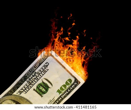 Smoke rises from a burning 100 dollar USA American dollar note. Black background with copy space area for finance related wealth designs and ideas.