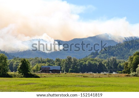 Smoke rises from the Douglas Complex forest fires near Glendale Oregon in steep rugged terrain of the southern coastal range mountains - stock photo
