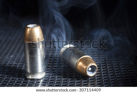 Smoke rising around a pair of handgun cartridges with hollow point bullets - stock photo