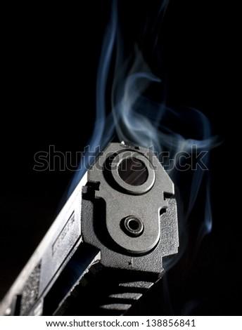 Smoke rising around the muzzle of a polymer handgun - stock photo