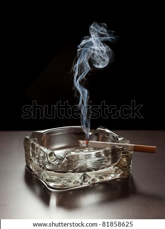 Smoke rising from a cigarette in an ashtray. - stock photo