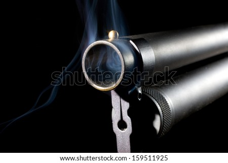 Smoke rising from a shotgun barrel with a black background - stock photo