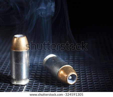 Smoke rising from handgun cartridges with hollow point bullets - stock photo